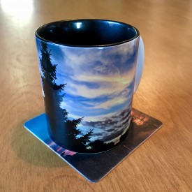 Evergreen silhouette against painted clouds - two-tone mug