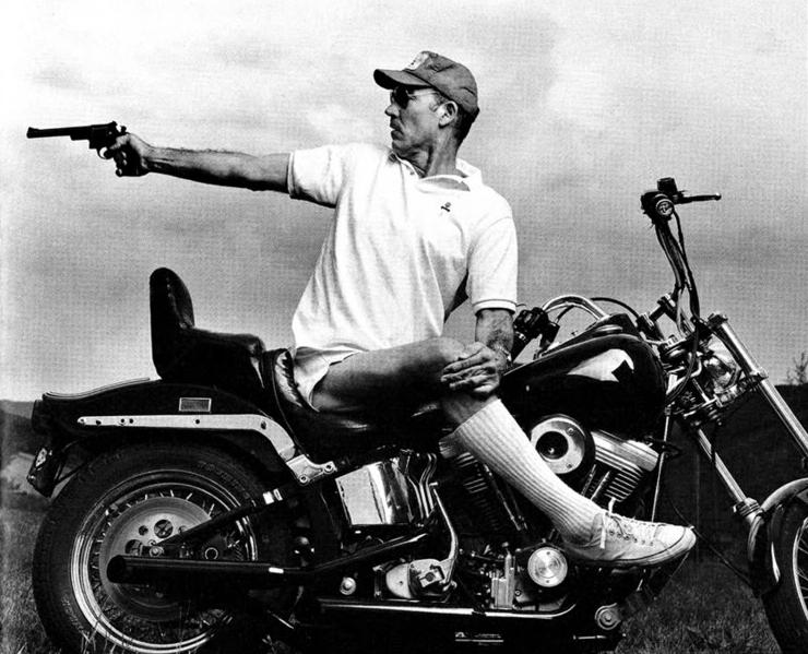 Hunter S. Thompson on a motorcycle with a gun