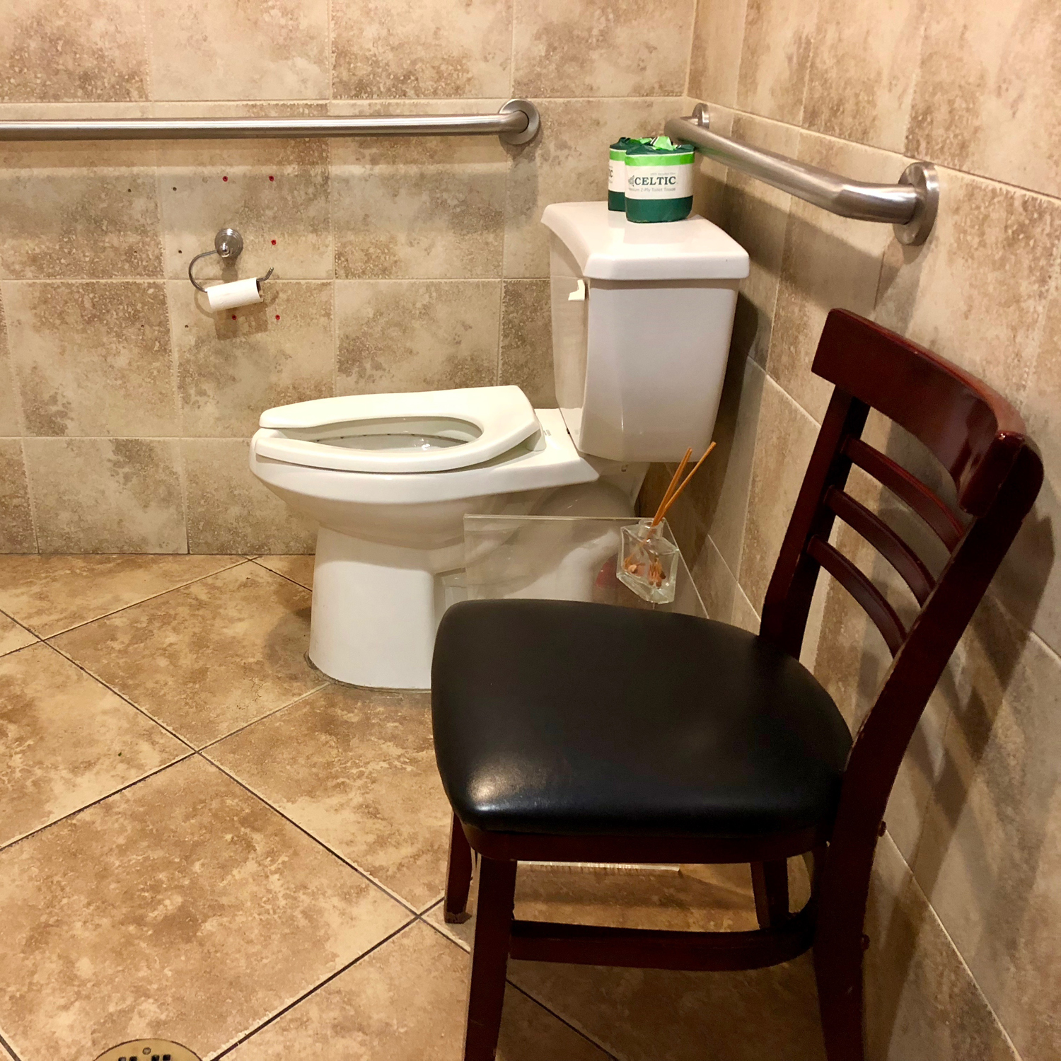 Restroom with a toilet and a chair